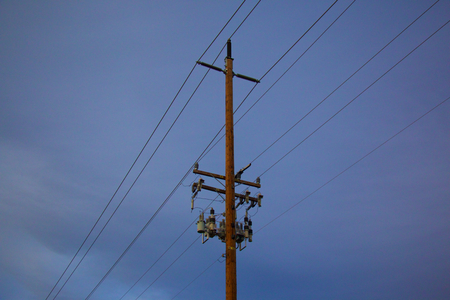 Pole and Power lines with blue background and clouds