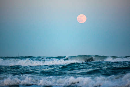 wild sea with full moon in background, focus on moon, blurry foreground 写真素材