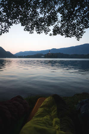 Early morning lake Bled in Slovenia. Calm lake, rising sun behind the mountains, Alps. Sleeping bags in the foreground, Outdoor Adventure in the Triglav National Park.