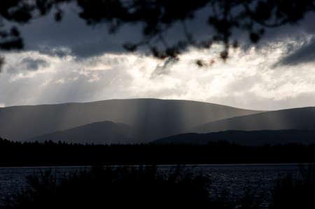 Silouhette of a mountian range behind a lake in the evening. Scottish highlands, Loch Morlich, Glen More, Cairngorms National Park Standard-Bild