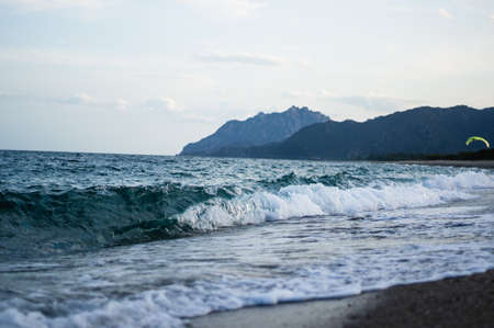 detail shot of wave splashing to the beach, mountains in the background.