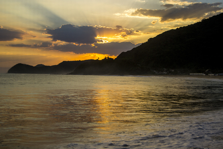 bather: Sunset on the Brazilian beach with sun reflecting in the sea