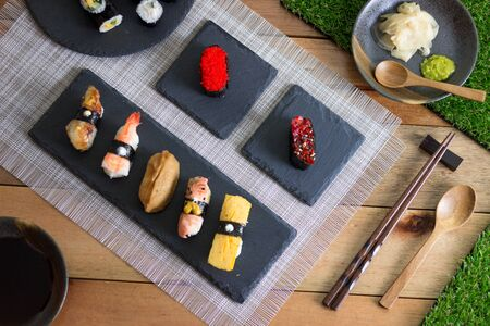 Sushi Variety on Wooden Table Stock Photo - 129441433