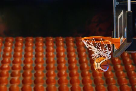 The basketbal on hoop in the gym Stock Photo