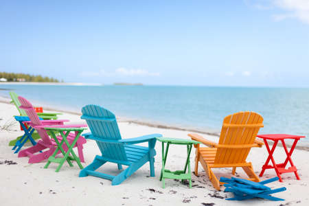 Colorful chairs on a beach by the sea.