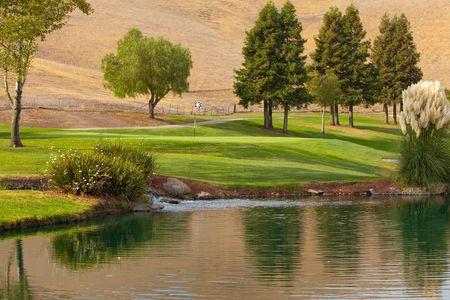 늦은 오후 햇빛에 물 위험 옆에 녹색 아름다운 골프 코스