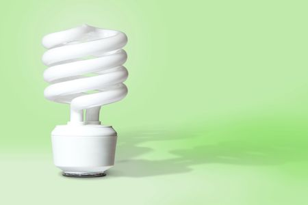 Compact fluorescent light bulb with shadows on light green background with room for copy