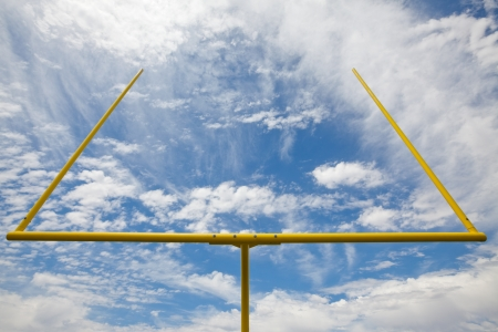 Yellow American football field goal metal uprights against a partially cloudy sky  Viewed from below and the front of the field goal