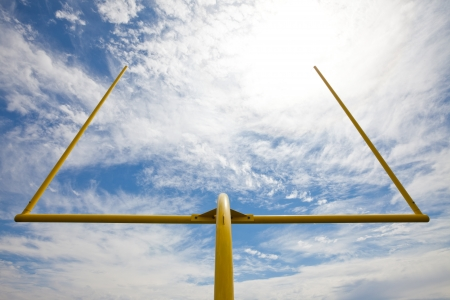 field goal: Yellow american footbal uprights against a partially cloudy sky  Viewed from below and the back of the field goal