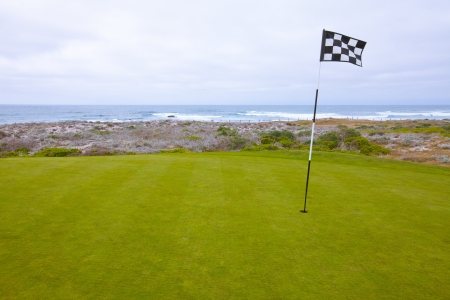 Beautiful putting green and pin flag fluttering in the ocean breeze Фото со стока
