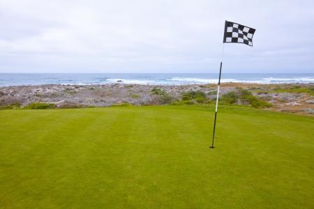 Beautiful putting green and pin flag fluttering in the ocean breeze Reklamní fotografie
