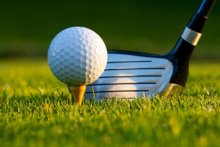golf green: Golf ball on tee in front of driver on a gold course  Stock Photo