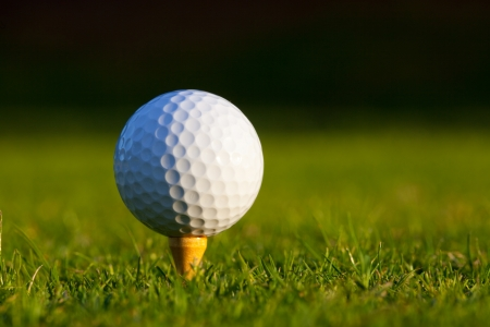 Golf ball on tee on manicured golf course grass  Stock Photo