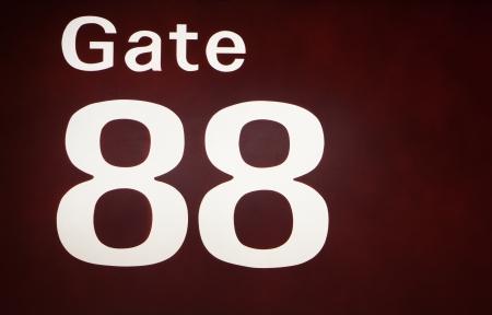 Closeu-up of an illuminated sign for gate 88 at an airport  Stock Photo