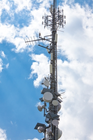 Cell phone tower under partially cloudy sky  Vertical format  Stock Photo