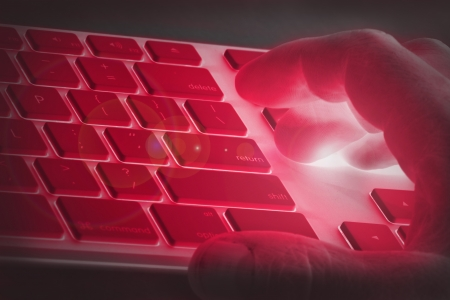 Hand on a keyboard with red lighting signifying danger, adult or off limits online use, e g  hacking, fraud, online scams or hacker activity  Stock Photo