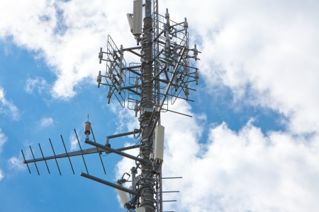 Cell phone tower under partially cloudy sky  Horizontal format