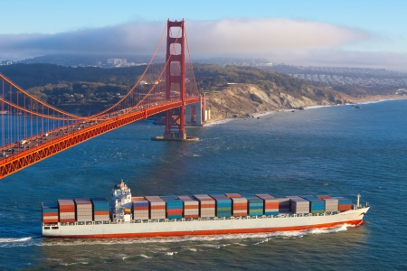 Full container cargo ship leaving San Francisco bay under the Golden gate bridge in the late afternoon photo