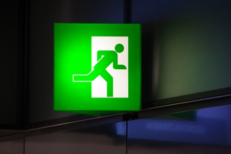 Illuminated green exit sign attached to a wall in a public transportation facility  Signage consists of a human figure running and exiting through a door opening  Stock Photo