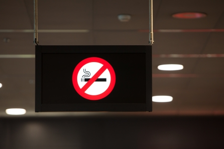 A black, illuminated non smoking sign with a red