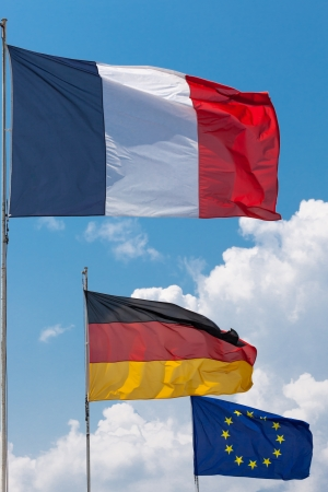 French, German and European Union Flags flying in the wind under a sun filled sky with towering cumulus clouds in the background