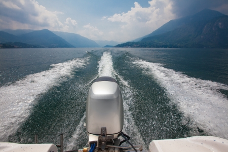 View of engine and wake of powerboat speeding across lake Como in Italy on a sunny day with cumulus clouds in the background surrounded by mountains with storm clouds rising above the mountain peaks Stock Photo