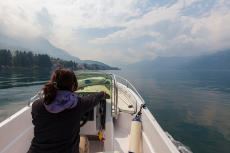 small boat: Woman piloting a small watercraft motor boat on a glassy smooth mountain lake  Its a sunny summer morning on lake Como in Italy  Clouds over the mountains are dispersing with the morning sun