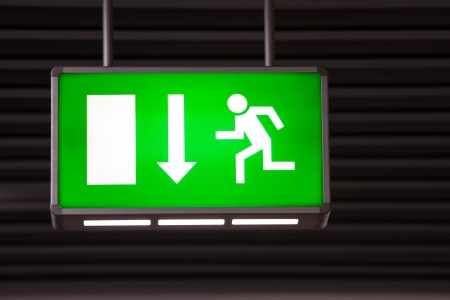 Illuminated green exit sign attached to the ceiling in a public transportation facility. Signage consists of a human figure running and exiting through a door opening.