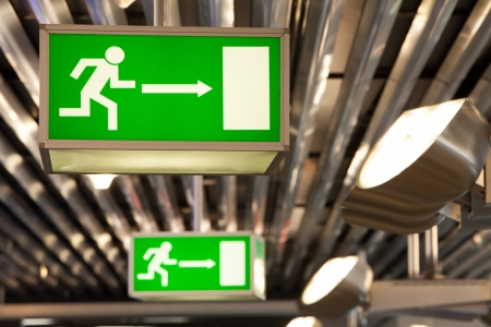 Illuminated green exit signs attached to the ceiling in a public transportation facility. Signage consists of a human figure running and exiting through a door opening. Lights shine light on ceiling and the signs.