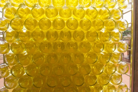 concave: A large cage full of white wine bottles lying on their sides with the concave bottoms of the bottles visible. The bottles in a wine production step after aging in their bottles.