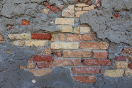 comprising: Mix of traditional bricks and natural stone bricks comprising an older, rustic exterior house wall. A thin layer of gray concrete covers the older brick wall architecture. The bricks have colors ranging from light beige to a traditional brick red. Stock Photo