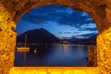 Rock arch opening overlooking lake Como in Italy on a tranquil evening. Lights from Menaggio village twinkling at the base of the mountains in the distance.