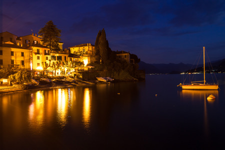Nightfall overlooking part of the town Varenna on lake Como. Buildings and a sailboat are illuminated by multiple lights reflecting on the water photo