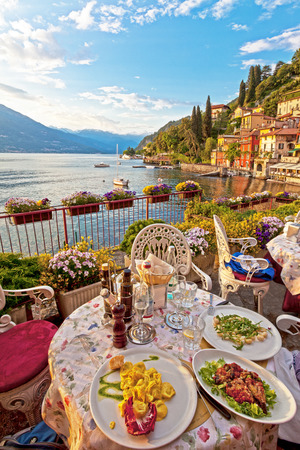 Dinner lakeside at Lake Como. Three plates of lovely vegetarian Italian food on white plates on a table on a lovely terrace overlooking a beautiful calm lake hills with antique buildings and alpine mountains in the background