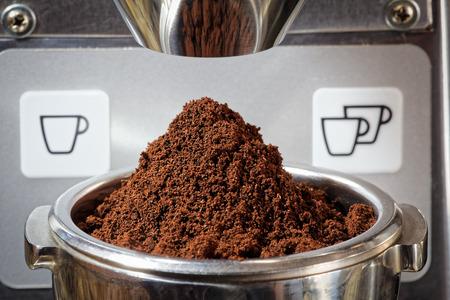 terreno: Primo piano di un mucchio di freshly terra chicchi di caffè per un espresso. Il caffè macinato finemente è nel portafiltro di metallo. L'immagine è presa con il portafiltro sotto lo scivolo metallico della smerigliatrice