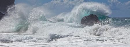 mare agitato: Il movimento delle onde potenti e spruzzare schiantarsi su incontaminato, costa rocciosa nella bellissima dinamica Pacifico scena costiera, spiaggia. Cielo azzurro, nuvole sullo sfondo. Na Pali costa, Kauai, Hawaii