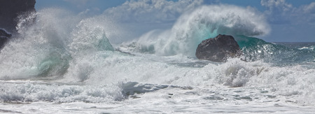 breaking wave: The motion of powerful waves and spray crashing on pristine, rocky shoreline   in beautiful dynamic Pacific ocean coastal, beach scene. Blue sky, clouds in the background. Na Pali coast, Kauai, Hawaii