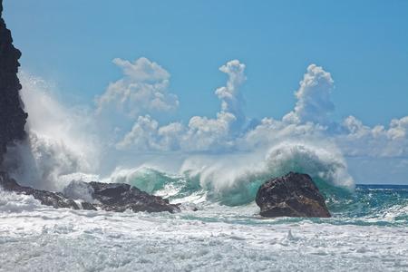 Powerful wave splash as it breaks on rocky shoreline. Dynamic coastal scene, tropical Pacific island; Na Pali coast, Kauai, Hawaii. Large wave spray with blue sky in background.