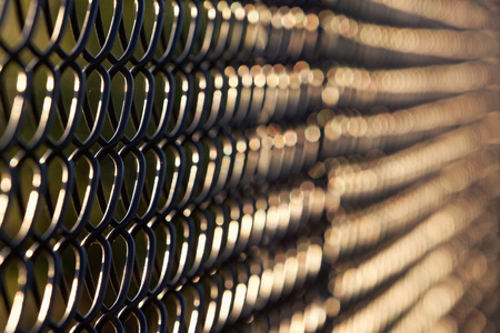 Artistic abstract view of black chain link fence in  late afternoon, early evening sunlight.