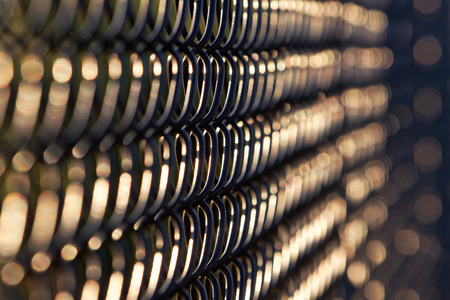 perimeter: Artistic abstract view of black chain link fence in  late afternoon, early evening sunlight.