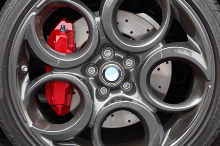 alloy: Close-up of gray, painted light weight, alloy wheel with a modern design featuring large circles. The red brake calipers stand out. Drilled disc brake. Low profile sports car tires. Alfa Romeo 4c.