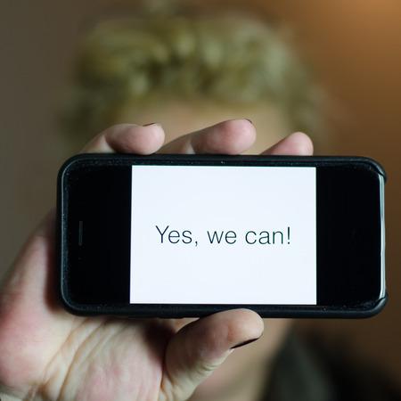 arrogancia: Mujer con el mensaje Yes, we can en el smartphone