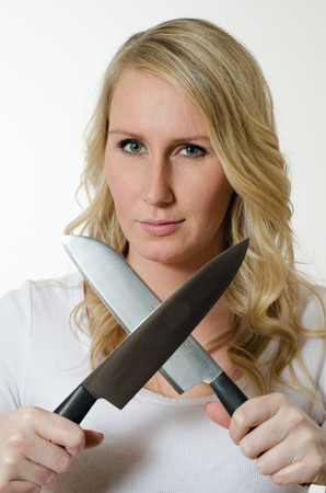 knifes: young woman sharpens knifes Stock Photo