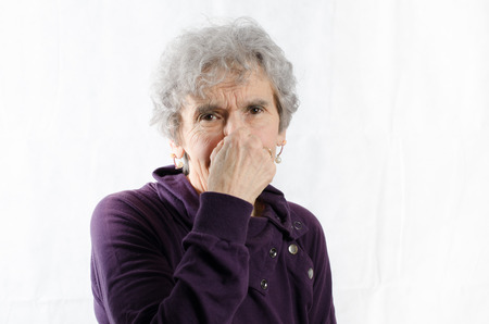 stinks: old woman is holding her nose