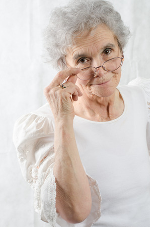 old woman looks over her glasses Stock Photo