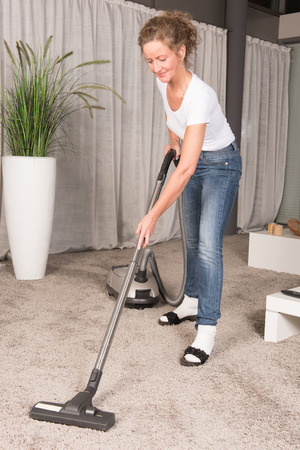 vacuum cleaning: woman vacuum cleaning the carpet Stock Photo