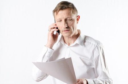 important phone call: businessman with papers on the phone Stock Photo