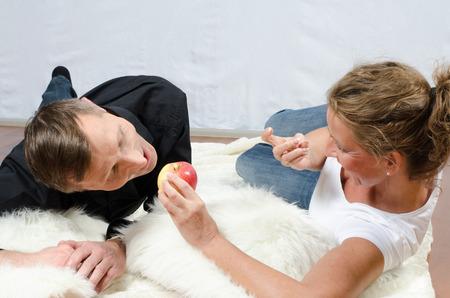 teasing: woman teasing man with apple Stock Photo