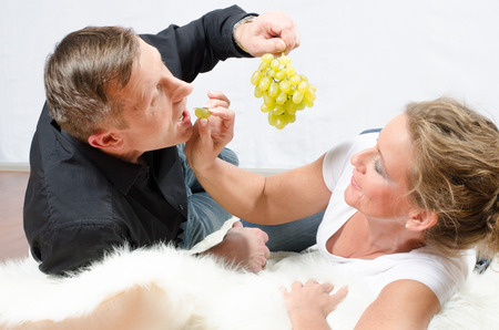 to tease: man teasing woman with grapes Stock Photo