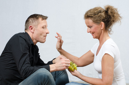 to tease: couple eating grapes